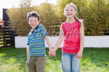 Portrait of smiling boy and girl holding hands in backyard Stock Photo - Premium Royalty-Freenull, Code: 635-05656164