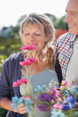 Senior couple smelling flowers in garden Stock Photo - Premium Royalty-Freenull, Code: 635-05656172