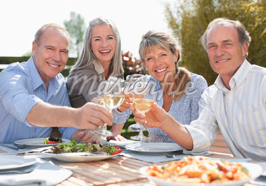 Portrait of smiling senior couples toasting wine glasses at patio table Stock Photo - Premium Royalty-Freenull, Code: 635-05656214