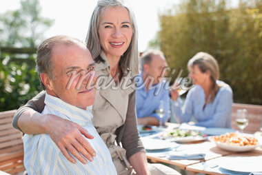 Portrait of senior couple enjoying lunch at table in sunny garden with friends Stock Photo - Premium Royalty-Freenull, Code: 635-05656284
