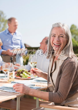 Portrait of smiling senior woman enjoying lunch with friends at sunny table Stock Photo - Premium Royalty-Freenull, Code: 635-05656298