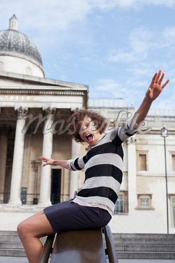 Portrait of exuberant woman with arms outstretched sliding on railing in front of historical landmark Stock Photo - Premium Royalty-Freenull, Code: 635-05656374