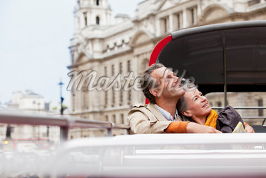 Smiling couple looking up on double decker bus in London Stock Photo - Premium Royalty-Freenull, Code: 635-05656378