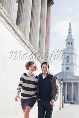 Happy couple walking along sunny urban buildings Stock Photo - Premium Royalty-Freenull, Code: 635-05656394