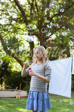 Girl blowing bubbles in backyard Stock Photo - Premium Royalty-Freenull, Code: 635-05656478
