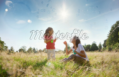 Mother and daughter blowing bubbles in sunny rural field Stock Photo - Premium Royalty-Freenull, Code: 635-05656497