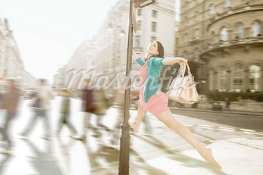 Mid adult woman in pink dress leaping through city streets Stock Photo - Premium Royalty-Freenull, Code: 614-05662200