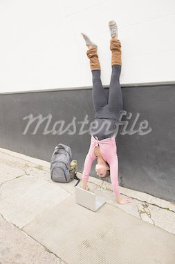 Woman performing handstand and using laptop on pavement Stock Photo - Premium Royalty-Freenull, Code: 614-05662210