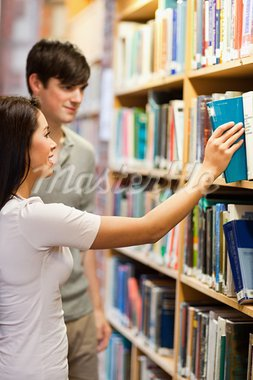 Portrait of students choosing a book on a shelf in a library Stock Photo - Royalty-Free, Artist: 4774344sean                   , Code: 400-05668953