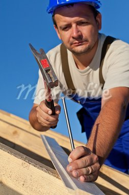 Carpenter working on the roof driving a nail in - shallow depth Stock Photo - Royalty-Free, Artist: lightkeeper                   , Code: 400-05670245