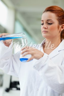 Portrait of a scientist pouring blue liquid in an Erlenmeyer flask in a laboratory Stock Photo - Royalty-Free, Artist: 4774344sean                   , Code: 400-05670338