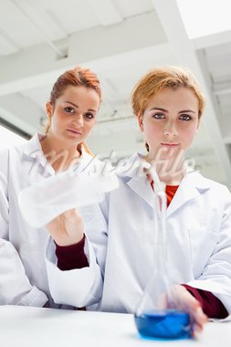 Portrait of cute science students doing an experiment while looking at the camera Stock Photo - Royalty-Free, Artist: 4774344sean                   , Code: 400-05670454