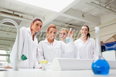 Smiling chemistry students holding a flask while looking at the camera Stock Photo - Royalty-Free, Artist: 4774344sean                   , Code: 400-05670630