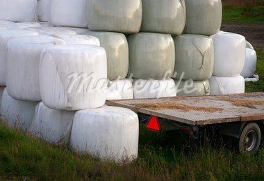 Stack of hay bales wrapped in plastic and an empty trailer Stock Photo - Royalty-Free, Artist: PinkBadger                    , Code: 400-05674949