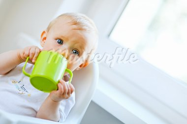 Pretty baby  sitting in chair and drinking from baby cup    Stock Photo - Royalty-Free, Artist: citalliance                   , Code: 400-05679436