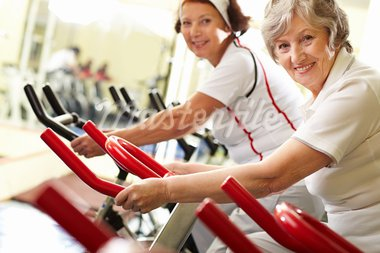 Portrait of two good-looking senior women training on exercise machines Stock Photo - Royalty-Free, Artist: pressmaster                   , Code: 400-05680478
