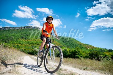 young athletic girl rides a bicycle on a mountain road Stock Photo - Royalty-Free, Artist: GekaSkr                       , Code: 400-05689705