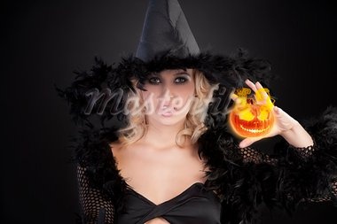 young beautiful woman in witch black dress with hat and a long gown pulling face, making a spell Stock Photo - Royalty-Free, Artist: carlodapino                   , Code: 400-05691064