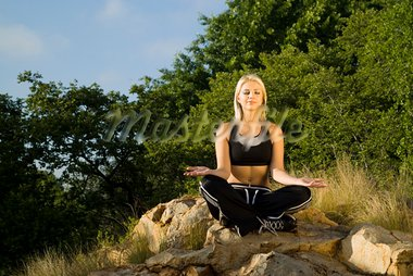 Pretty woman meditating on rock eyes closed with gold light reflector Stock Photo - Royalty-Free, Artist: alistaircotton                , Code: 400-05694398