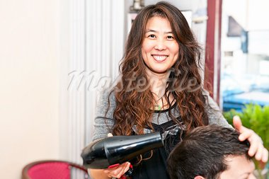 Smiling hairstylist drying hair with hairdryer in her salon Stock Photo - Royalty-Free, Artist: Elenathewise                  , Code: 400-05695754