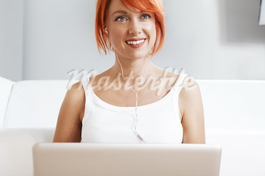 Caucasian redhead woman wearing headphones and listening music Stock Photo - Royalty-Free, Artist: fotum                         , Code: 400-05704595