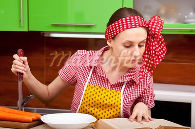 Serious woman in the kitchen with knofe is reading recipe book Stock Photo - Royalty-Free, Artist: Iryna_Rasko                   , Code: 400-05705201