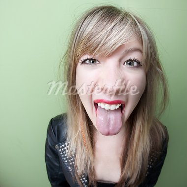 Cute young woman sticks out her tongue over green background Stock Photo - Royalty-Free, Artist: creatista                     , Code: 400-05706835