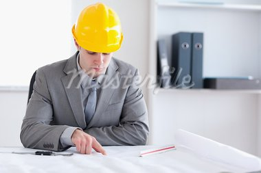 Architect sitting behind a table and working on a building plan Stock Photo - Royalty-Free, Artist: 4774344sean                   , Code: 400-05709505