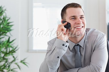 Smiling businessman getting a pleasant call on his mobile phone Stock Photo - Royalty-Free, Artist: 4774344sean                   , Code: 400-05710253