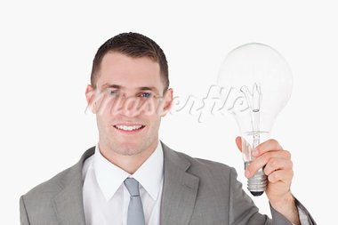 Businessman holding a bulb against a white background Stock Photo - Royalty-Free, Artist: 4774344sean                   , Code: 400-05715103