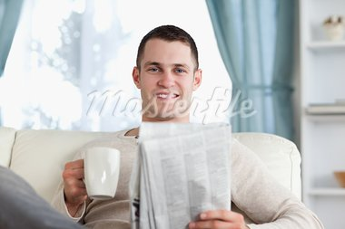 Young man having a tea while reading the news in his living room Stock Photo - Royalty-Free, Artist: 4774344sean                   , Code: 400-05715359