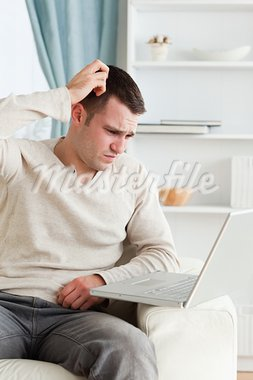 Portrait of a confused man using a notebook in living room Stock Photo - Royalty-Free, Artist: 4774344sean                   , Code: 400-05715555