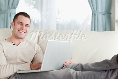 Smiling man relaxing with a notebook in his living room Stock Photo - Royalty-Free, Artist: 4774344sean                   , Code: 400-05715589
