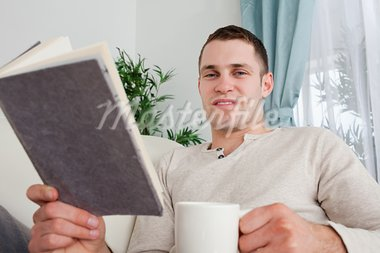 Man holding a cup of coffee and a book in his living room Stock Photo - Royalty-Free, Artist: 4774344sean                   , Code: 400-05715629