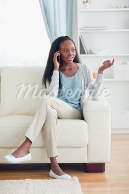 Young woman talking on the phone while sitting on the sofa Stock Photo - Royalty-Free, Artist: 4774344sean                   , Code: 400-05716403
