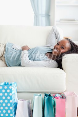 Smiling woman lying on sofa after shopping Stock Photo - Royalty-Free, Artist: 4774344sean                   , Code: 400-05716959