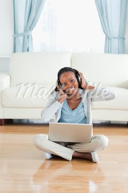 Smiling woman sitting on the floor listening to music Stock Photo - Royalty-Free, Artist: 4774344sean                   , Code: 400-05717177