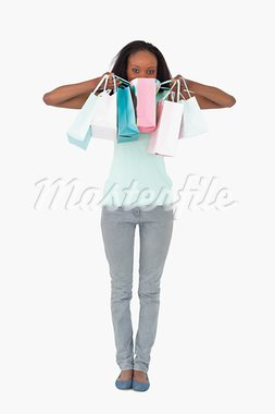 Young woman hiding behind her shopping on white background Stock Photo - Royalty-Free, Artist: 4774344sean                   , Code: 400-05717289