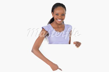 Smiling woman pointing on placeholder beneath her on white background Stock Photo - Royalty-Free, Artist: 4774344sean                   , Code: 400-05717397
