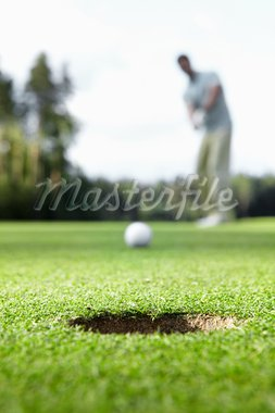 A man scores ball in the hole Stock Photo - Royalty-Free, Artist: Deklofenak                    , Code: 400-05717907