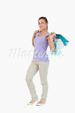 Side view of young female with shopping bags against a white background Stock Photo - Royalty-Free, Artist: 4774344sean                   , Code: 400-05718656