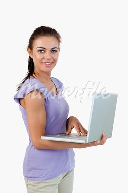 Smiling young female with laptop against a white background Stock Photo - Royalty-Free, Artist: 4774344sean                   , Code: 400-05718704