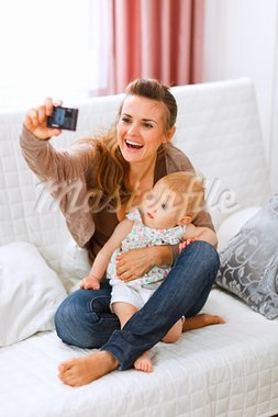 Beautiful young mom making photos with her lovely baby at home  Stock Photo - Royalty-Free, Artist: citalliance                   , Code: 400-05723089