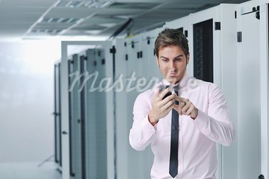 young business man computer science engeneer talking by cellphone at network datacenter server room asking  for help and fast solutions and services Stock Photo - Royalty-Free, Artist: dotshock                      , Code: 400-05728702
