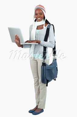 Side view of female student in winter clothing and laptop against a white background Stock Photo - Royalty-Free, Artist: 4774344sean                   , Code: 400-05728914