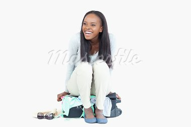 Laughing woman can't get her suitcase closed against a white background Stock Photo - Royalty-Free, Artist: 4774344sean                   , Code: 400-05729199