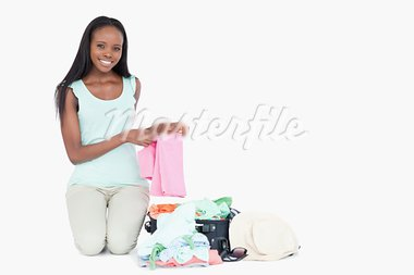 Smiling young woman packing her trunk against a white background Stock Photo - Royalty-Free, Artist: 4774344sean                   , Code: 400-05729208