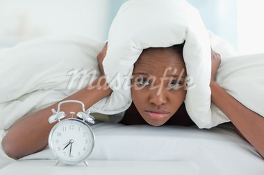 Exhausted woman covering her ears with a duvet while her alarm clock is ringing Stock Photo - Royalty-Free, Artist: 4774344sean                   , Code: 400-05729402