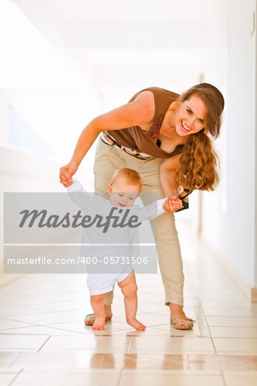 Happy mom helping baby to walk  Stock Photo - Royalty-Free, Artist: citalliance                   , Code: 400-05731506