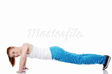 Pretty teen caucasian girl doing exercises on the floor over white background. Stock Photo - Royalty-Free, Artist: BDS                           , Code: 400-05732663